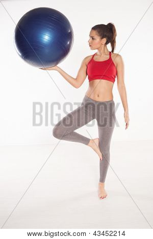 Woman using a pilates ball balanced on one foot while holding the ball at shoulder height to promote muscle control