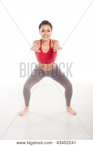 Smiling young woman full of vitality doing exercises in a gym facing towards the camera on a white studio background