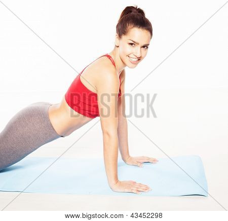 Smiling fit young woman doing press-ups looking sideways smiling at the camera, isolated studio portrait