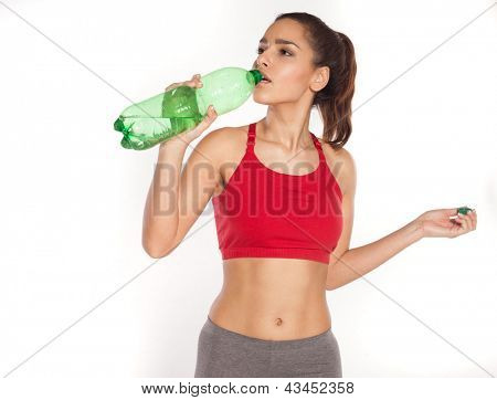 Sporty young woman drinking water from a large green plastic bottle isolated on white