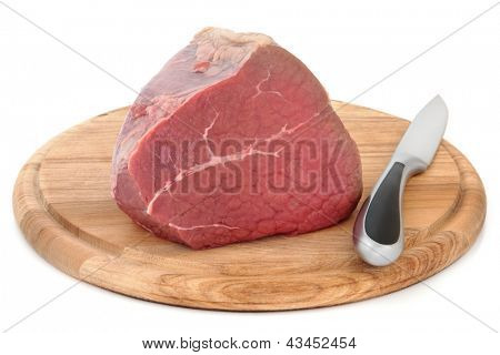 Silverside of beef meat joint on a carving board with knife over white background.