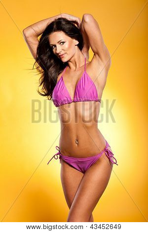 Sexy beautiful brunette woman with a lovely tan posing in a pink bikini with her arms raised against a yellow background