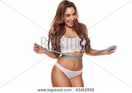 Beautiful vivacious young woman laughing as she stands measuring her waist isolated on white