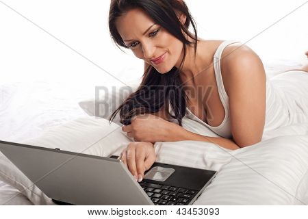Smiling beautiful young brunette woman lying on the bedclothes on her stomach using a laptop in bed