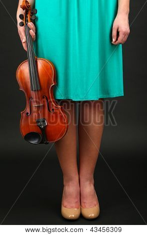 Young girl with violin on grey background
