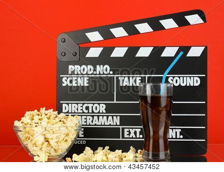 Movie clapperboard, cola and popcorn on red background
