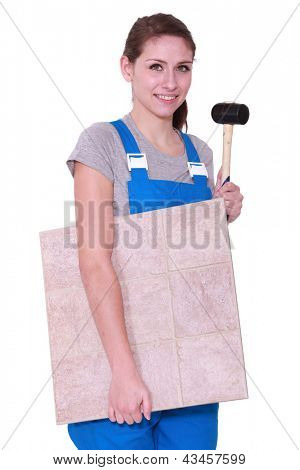 young woman holding tiles an a hammer