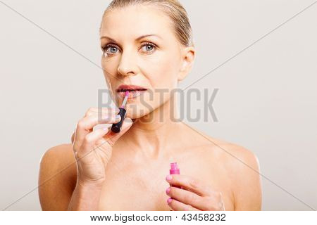 portrait of older woman putting lip gloss close up