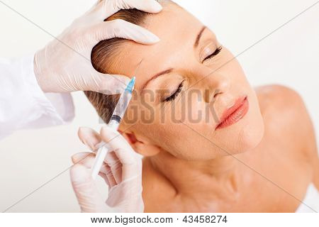 doctor giving face lifting injection on mature woman