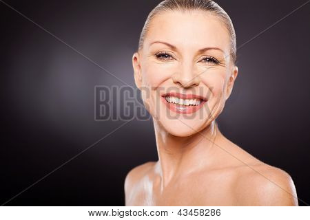 gorgeous mid age woman smiling against black background