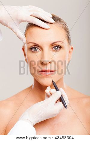 cosmetic surgeon marking mid age woman chin before plastic surgery