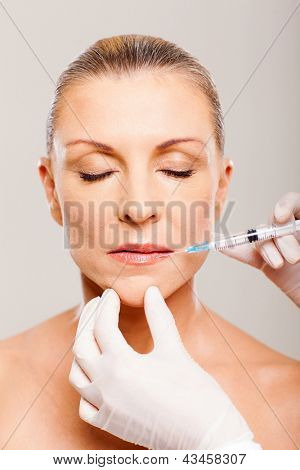 pretty mature woman receiving cosmetic injection on her lips