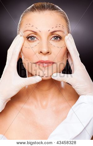 beautician doing skin check to older woman before face lifting surgery
