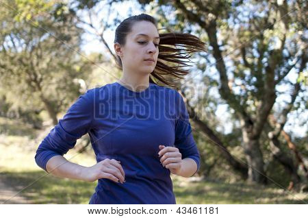 Very close up of woman jogging, facing right, empty space right