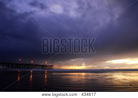 Stormy Sunset With Pier And Lights