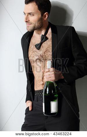 Sexy male model smoking cigar in open formal attire