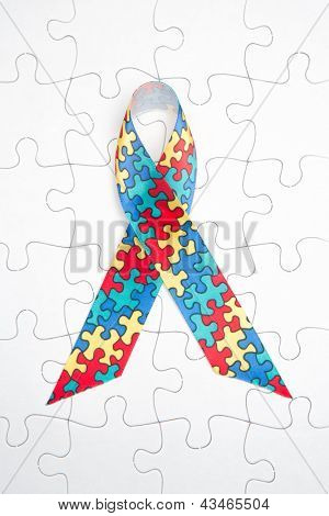 Awareness ribbon for autism and aspergers on white jigsaw background