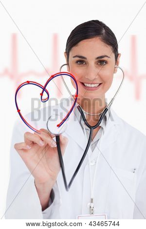 Happy doctor holding up stethoscope to heart design on ECG background