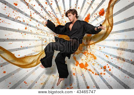 Martial arts expert mid air on linear pattern with orange paint splashes and vapour