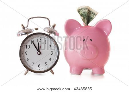 Dollar note sticking out of piggy bank beside alarm clock on white background