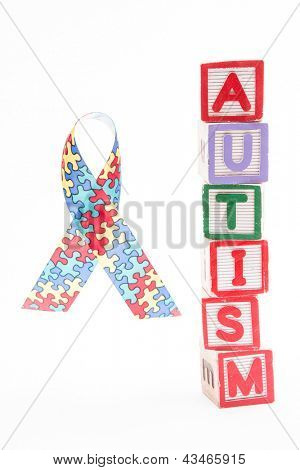 Autism awareness ribbon beside stacked blocks spelling autism on white background