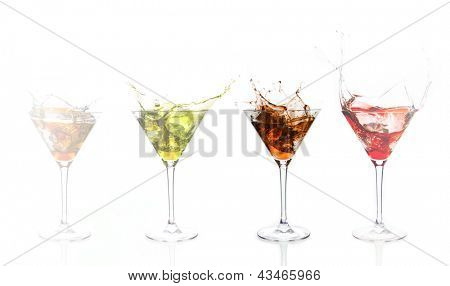 Serial arrangement of coloured alcohol splashing in cocktail glass on white background