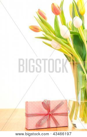 Vase of tulips on wooden table with pink wrapped gift