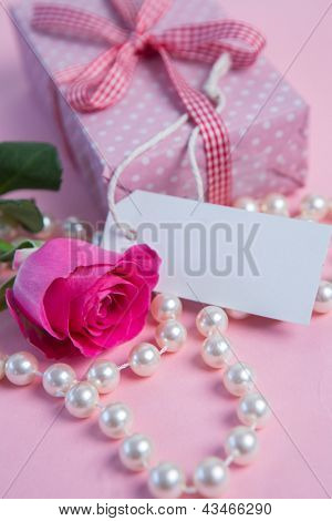 Pink rose with gift and string of pearls with blank tag on pink surface