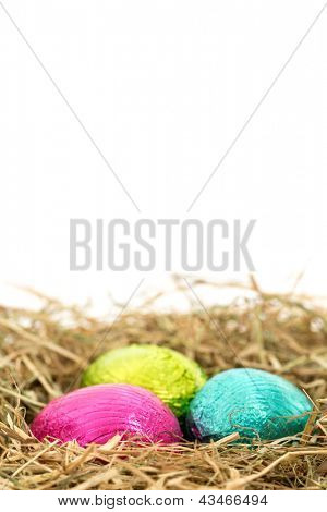 Three foil wrapped easter eggs nestled in straw nest with copy space