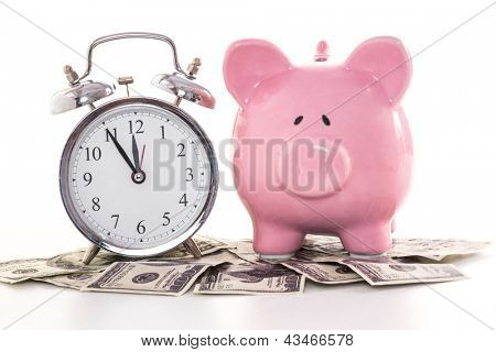 Pink piggy bank beside alarm clock on dollars on white background