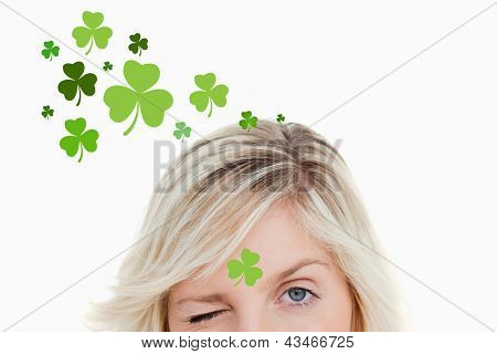 Blonde woman winking on shamrock background for st patricks day