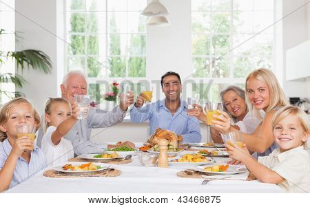 Happy family toasting around the table at thanksgiving dinner