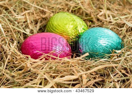Three colouful foil wrapped easter eggs nestled in straw nest