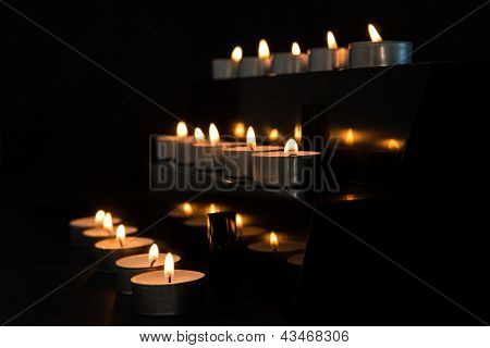 Tea light candles at the alter in the darkness