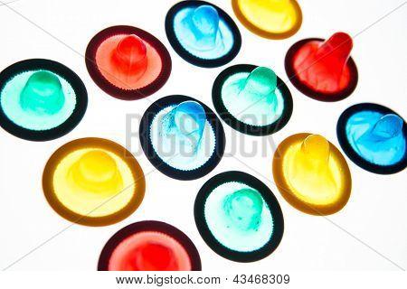 Twelve brightly coloured condoms on white background