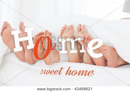 Home sweet home message on image of familys feet sticking out from under bed covers