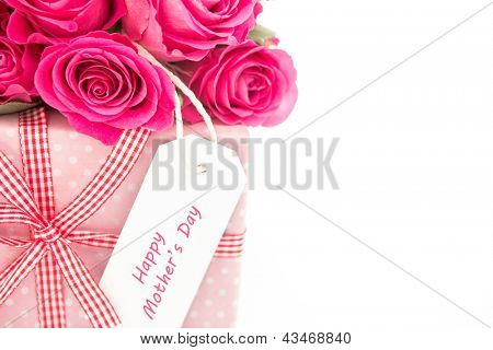 Close up of a bouquet of pink roses next to a pink gift with a happy mothers day card on a white background close up