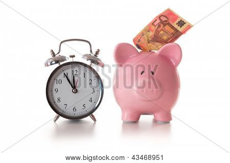 Alarm clock and piggy bank with fifty euro sticking out on white background