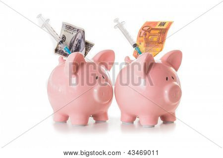 Dollar and euro notes and syringes sticking out of pink piggy banks on white background