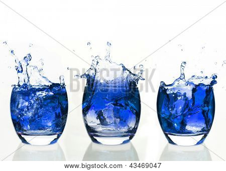 Serial arrangement of blue liquid splashing in tumbler on white background