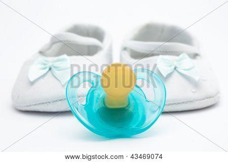 Chupeta azul com botinhas de bebé em fundo branco