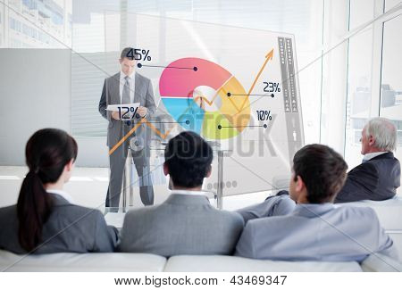 Business people listening and looking at colorful pie chart interface in a meeting