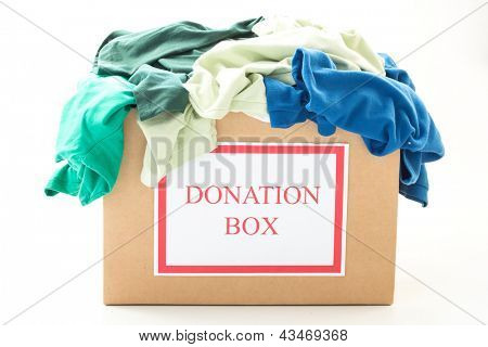 Cardboard donation box with clothes on white background