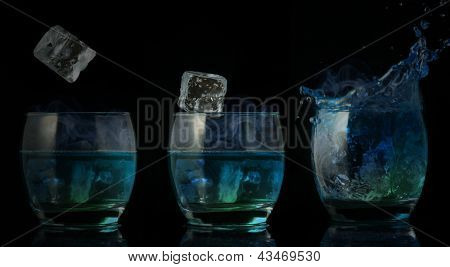 Serial arrangement of ice falling into glass tumbler of blue liquid on black background