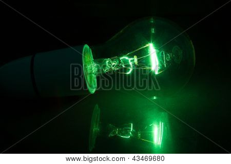 Green light bulb turned over on black background on reflective surface