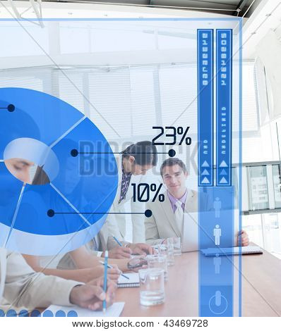 Serious business people using blue pie chart interface in a meeting