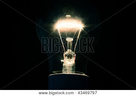 Dazzling filament bulb on background
