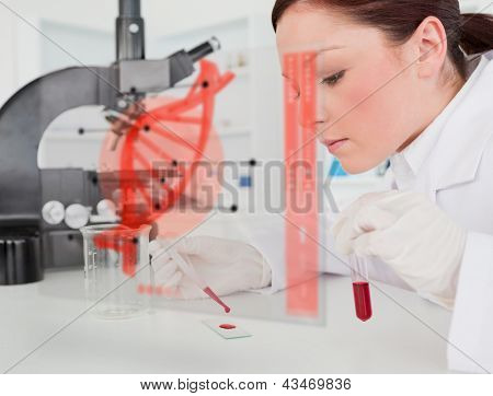 Scientist pouring drop of blood onto glass with futuristic interface in front of her showing DNA