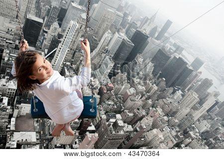 Menina balançando com a cidade ao fundo