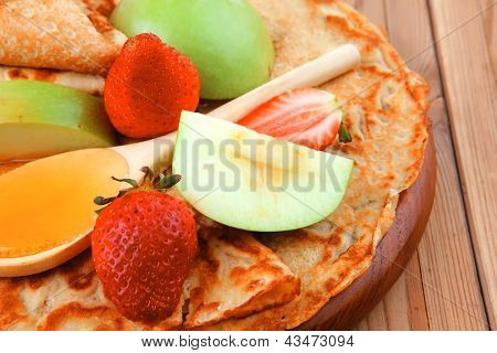 dessert : thin round pancake with honey strawberries and apple on wooden table